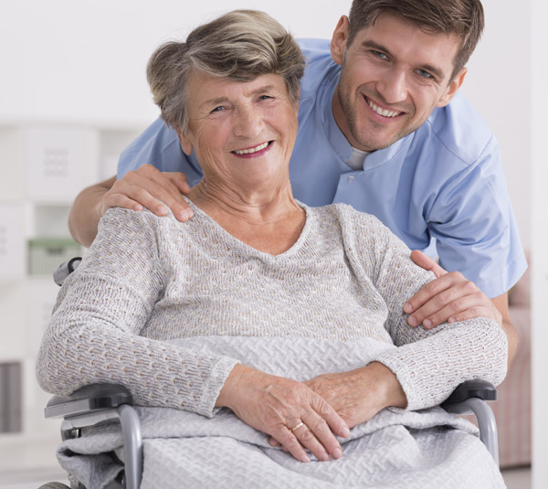 senior woman in a wheelchair with a male nurse for home care